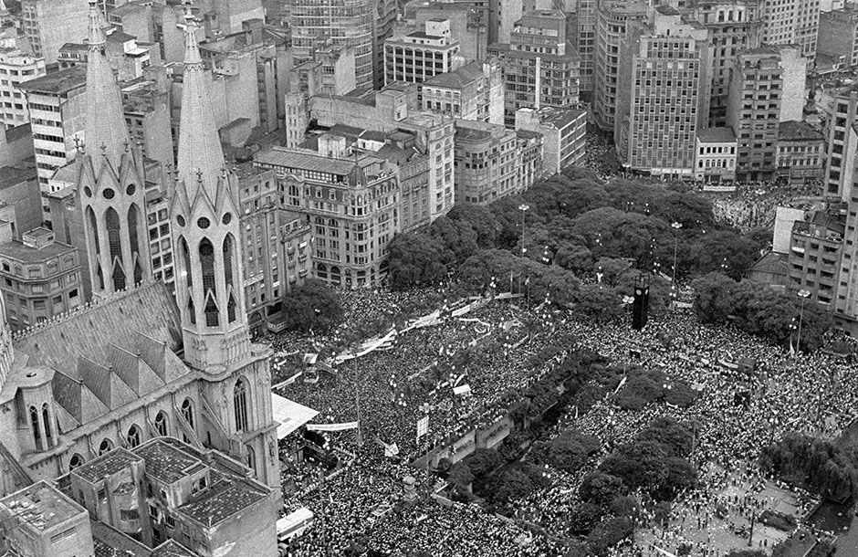 No dia do aniversário da cidade, 300 mil pessoas se reúnem na Praça da Sé para ouvir lideranças políticas e sindicais, intelectuais e artistas pedirem o voto direto para presidente e a redemocratização plena do país