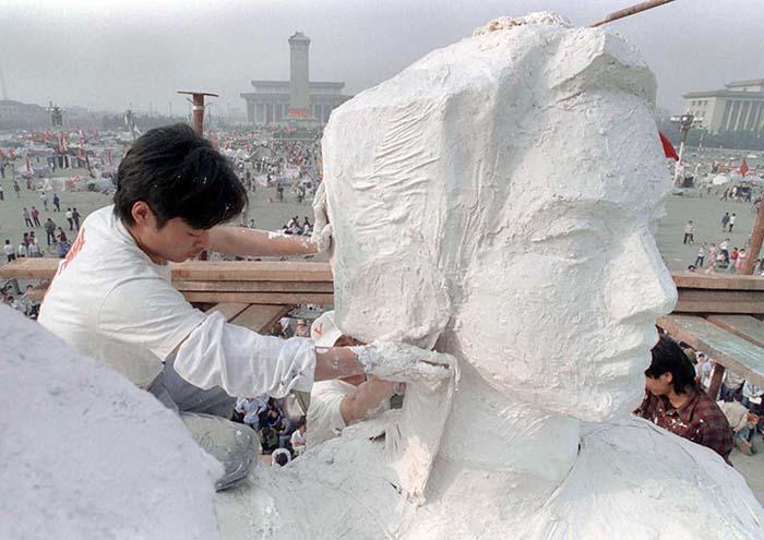 """Um estudante da faculdade de artes completa a estátua da """"deusa da democracia"""", em 30 de maio de 1989, durante os protestos na Praça da Paz Celestial"""