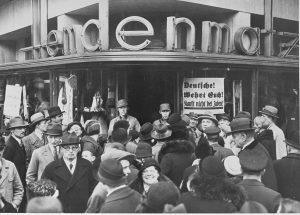 """Alemães em frente a uma loja de departamentos durante o boicote. No cartaz: """"Alemães! Protejam-se! Não comprem de judeus!"""""""
