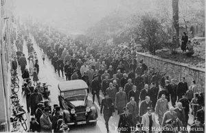Homens judeus aprisionados na Noite dos Cristais marcham em Berlim, sob a guarda das SS, para assistir à destruição de uma sinagoga, antes de serem deportados. Os que ficaram serão posteriormente submetidos ao holocausto.