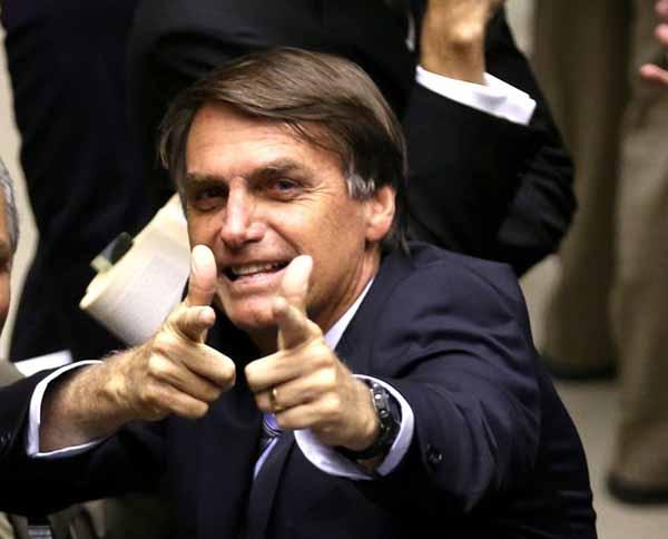 Com seu gesto característico, o presidente Jair Bolsonaro indica que o governo enxerga o Estado como uma milícia