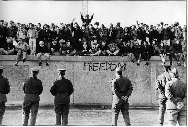 Estudantes da Alemanha Oriental no Muro de Berlim, diante de guardas de fronteira, em 9 de novembro de 1989