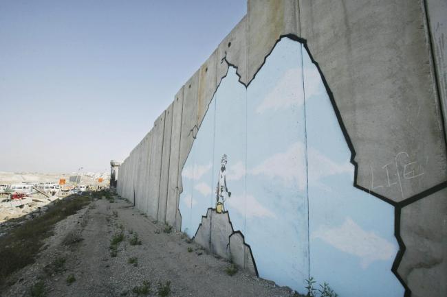"""Grafite do artista Banksy em seção da """"barreira de segurança"""" nos arredores de Ramallah"""